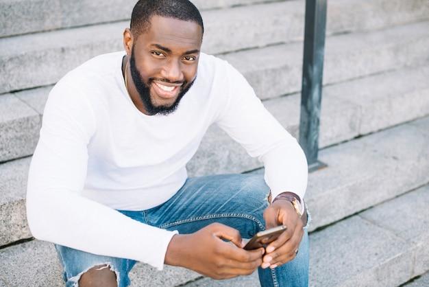 Homem, escada, segurando, smartphone
