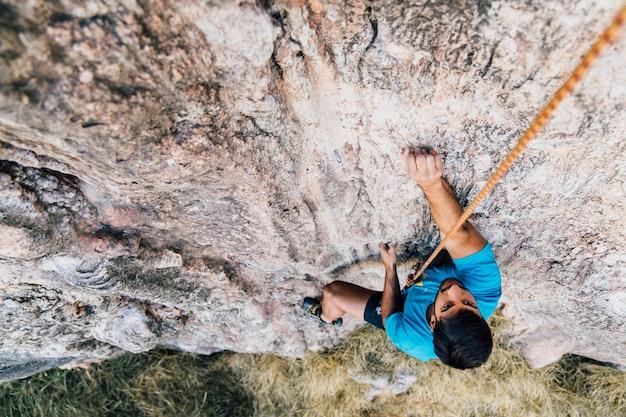 Homem escalando rock com corda