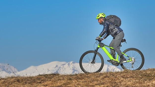 Homem escalando um prado na montanha com uma mountain bike