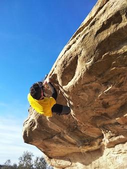 Homem escalando uma rocha alta nas montanhas. conceito de aventura e esporte radical