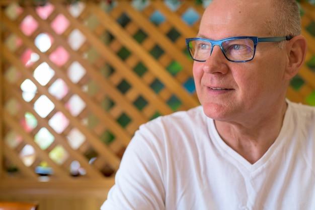 Homem escandinavo sênior sentado em um restaurante pronto para o café da manhã