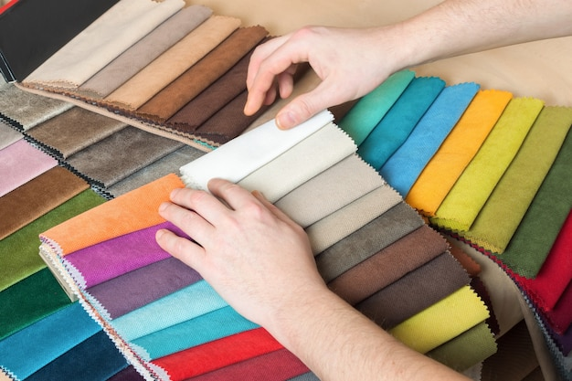 Homem escolhe amostras de tecido colorido na mesa de perto