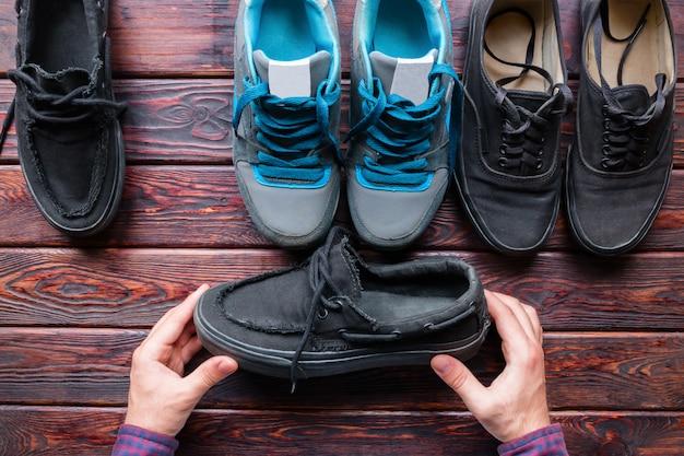 Homem escolhe sapatos segurando sapatos pretos