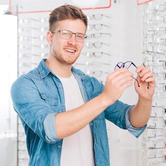 Homem escolhendo novos óculos no optometrista