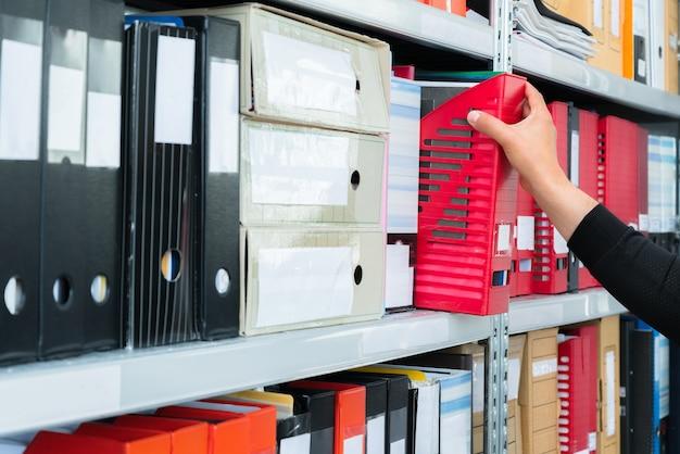 Homem escolhendo pasta cega com arquivos da estante