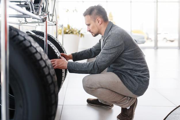Homem escolhendo pneus para carro novo no showroom.