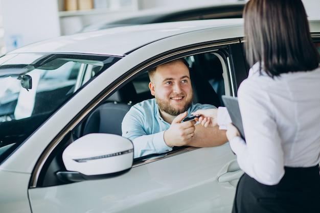 Homem escolhendo um carro em um salão de carros