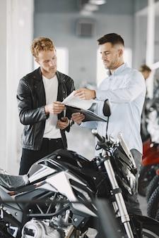Homem escolheu motocicletas na loja de motos. cara com uma jaqueta preta. gerente com cliente.