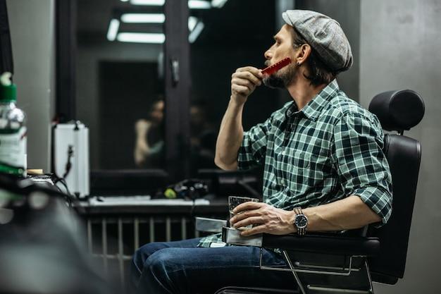 Homem escovando cuidadosamente a barba enquanto está em uma barbearia moderna