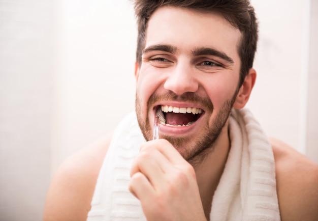Homem escovando os dentes e olhando no espelho.