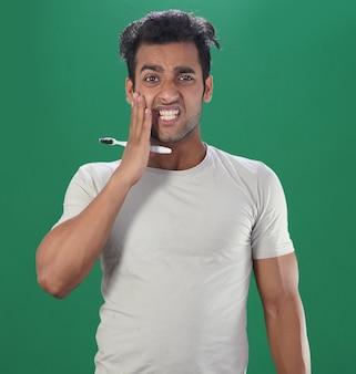 Homem escovando os dentes e tendo problemas de dor nos dentes