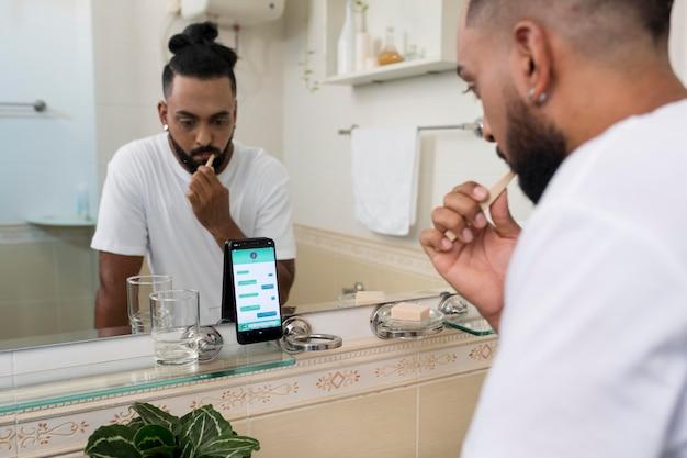Homem escovando os dentes enquanto verifica suas mensagens