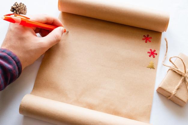 Homem escreve no pergaminho ao lado de um presente de natal