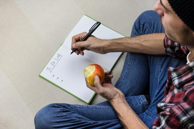 Homem escreve para fazer a lista no caderno