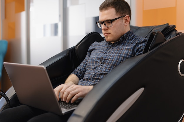 Homem escrevendo código enquanto está sentado na poltrona no escritório