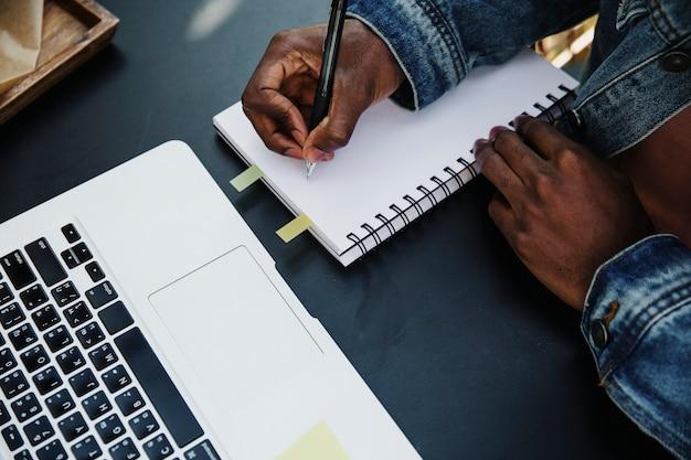 Homem escrevendo em seu caderno em um café