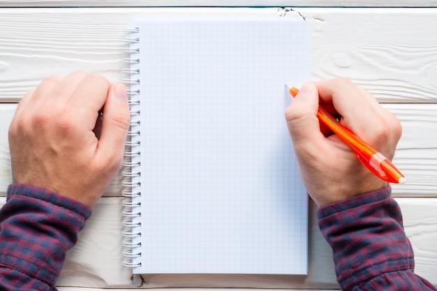 Homem escrevendo em um caderno sobre um fundo branco de madeira