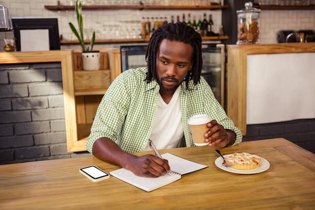 Homem escrevendo em um caderno
