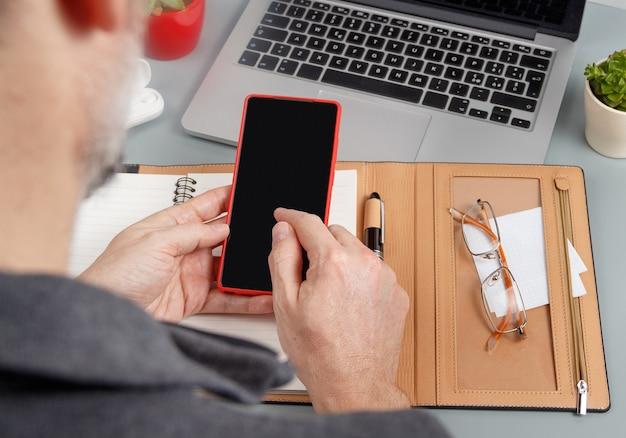 Homem escrevendo na agenda e usando o telefone celular em uma vista superior da mesa de escritório cinza. conceito de negócios