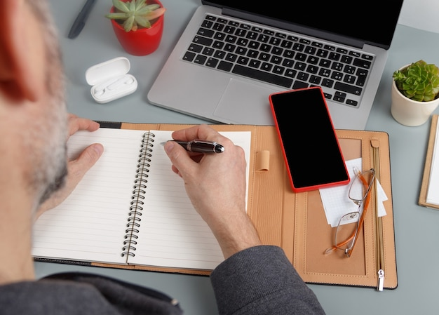 Homem escrevendo na agenda perto do laptop close-up. conceito de negócios. maquete de telefone