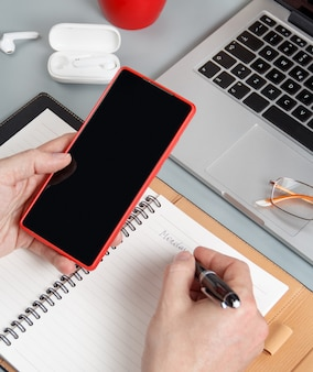 Homem escrevendo na agenda segunda-feira e usando o telefone celular em uma vista alta da mesa de escritório cinza. conceito de negócios