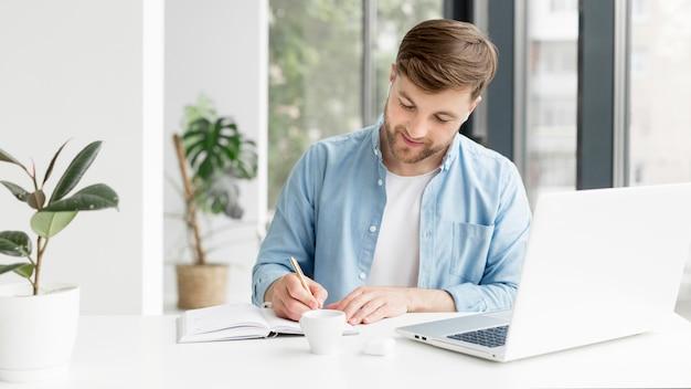 Homem escrevendo na agenda