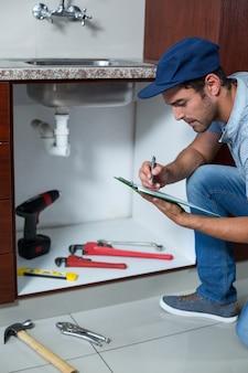 Homem escrevendo na área de transferência com ferramentas de trabalho