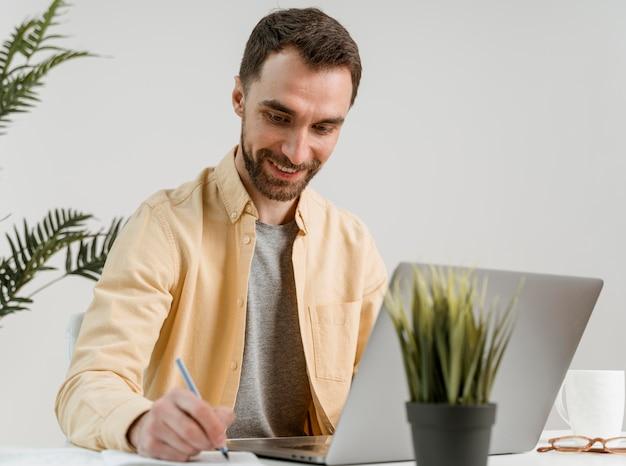 Homem escrevendo na aula de videochamada