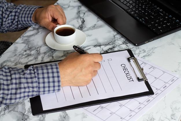 Homem escrevendo na lista de verificação e tomando café ao lado do laptop na mesa de mármore