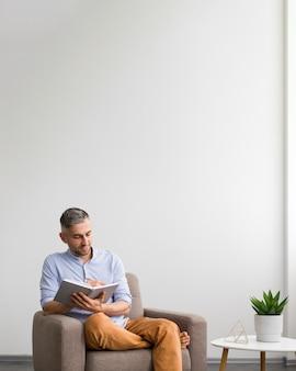 Homem escrevendo na sua agenda e copie o espaço