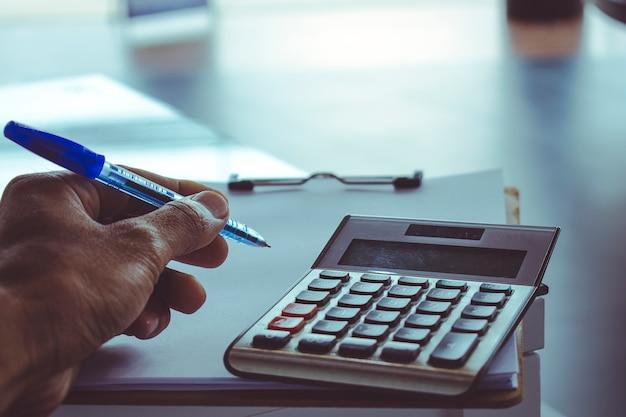 Homem escrevendo no bloco de notas ou nota sobre fundo desfocado de lista de preço