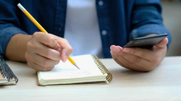 Homem escrevendo no notebook enquanto estiver usando telefone celular