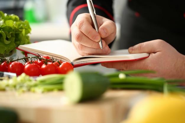 Homem escrevendo no notebook na cozinha