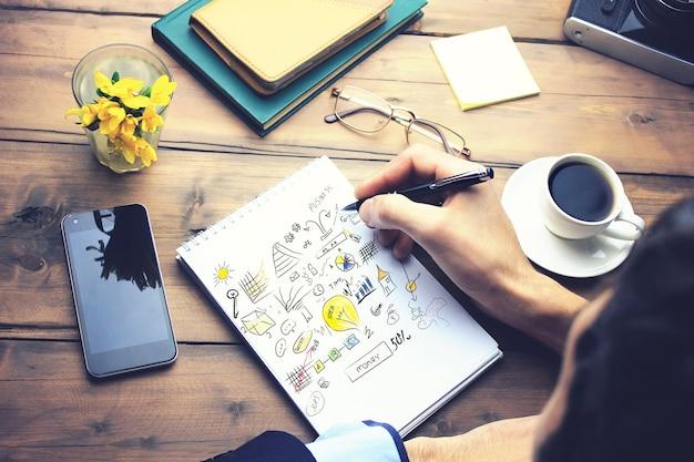 Homem escrevendo no papel da ideia na mesa de trabalho de madeira