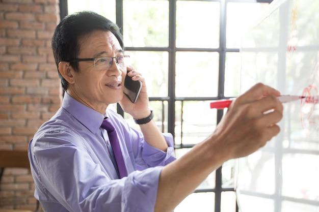Homem escrevendo no quadro branco e falando no telefone