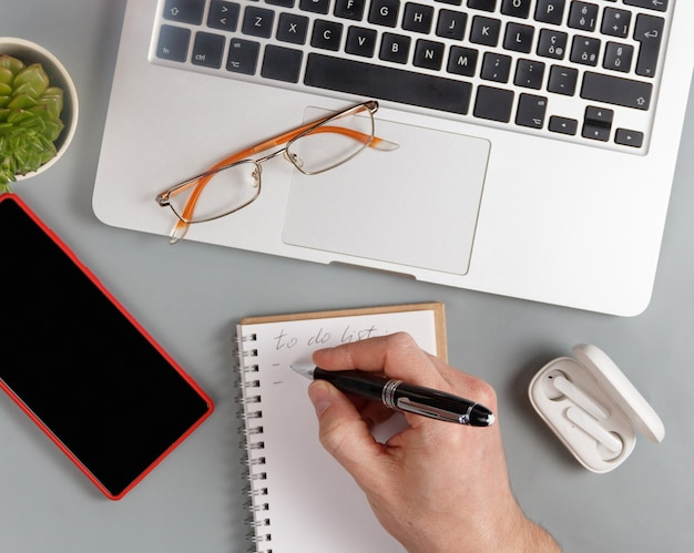 Homem escrevendo para fazer a lista na agenda em uma vista superior da mesa de escritório cinza. conceito de negócios