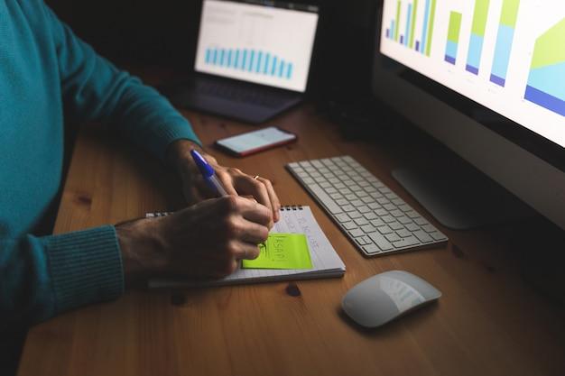Homem escrevendo para fazer a lista no escritório em casa, trabalhando à noite
