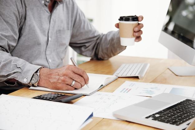 Homem escrevendo planos de negócios