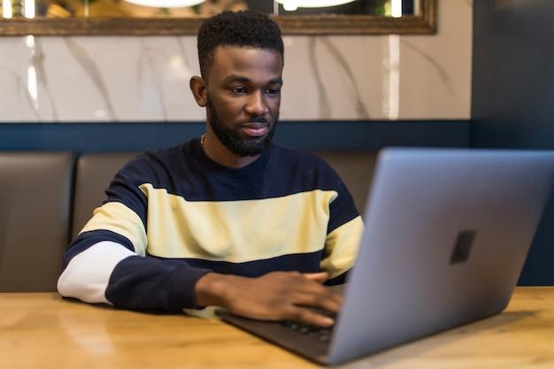 Homem escrevendo texto no laptop em um café moderno. estudante africano feliz navegando na web no laptop