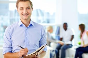 Homem escrita bem sucedida em sua agenda