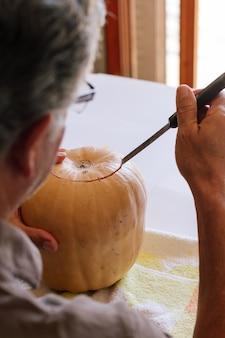 Homem esculpindo uma abóbora