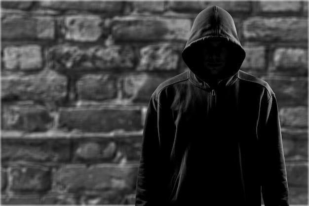 Homem escuro irreconhecível com capuz no fundo