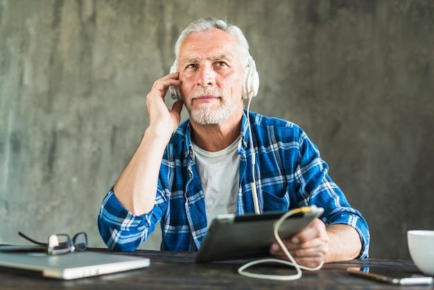 Homem, escutar, através, headphone, anexado, ligado, tablete digital