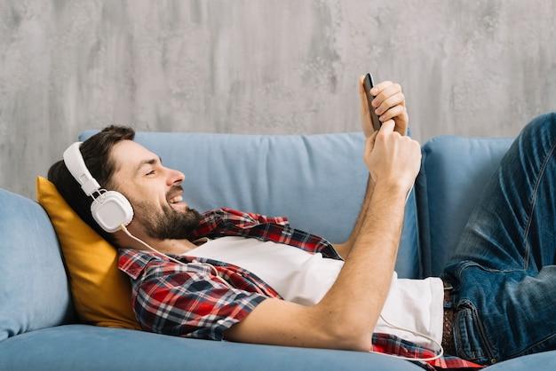 Homem, escutar música, e, usando, smartphone
