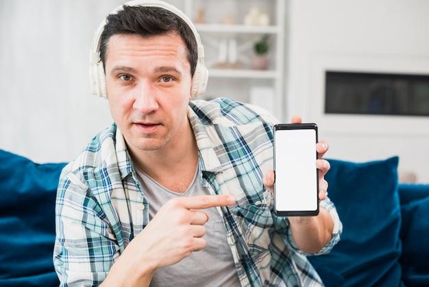 Homem, escutar música, em, fones, e, apontar, smartphone, ligado, canapé