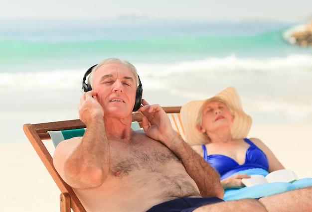 Homem, escutar música, enquanto, seu, esposa, é, dormir