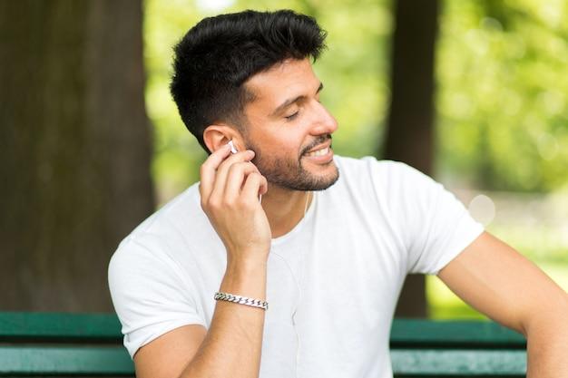 Homem, escutar música, sentando, ona, banco, em, um, parque, em, um, quentes, verão, ensolarado, dia