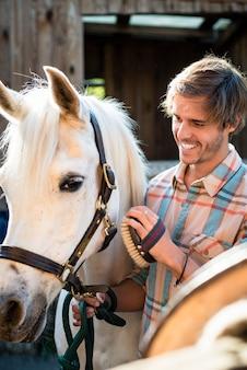 Homem esfregando cavalo branco
