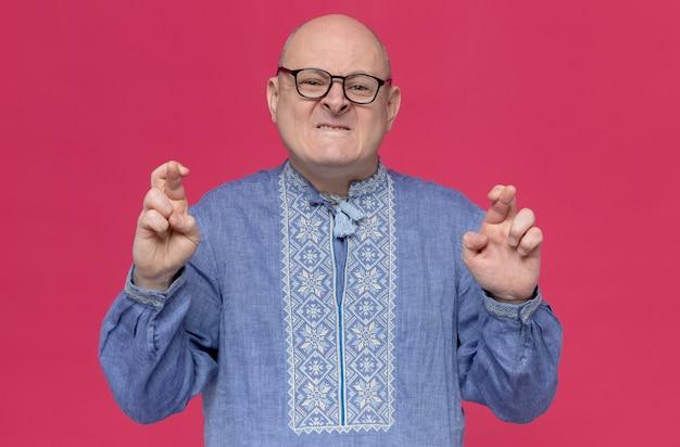 Homem eslavo adulto ansioso com camisa azul usando óculos ópticos cruzando os dedos e