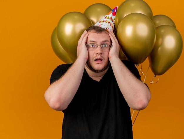 Homem eslavo adulto chocado com óculos ópticos e boné de aniversário coloca as mãos na cabeça e fica de pé na frente de balões de hélio